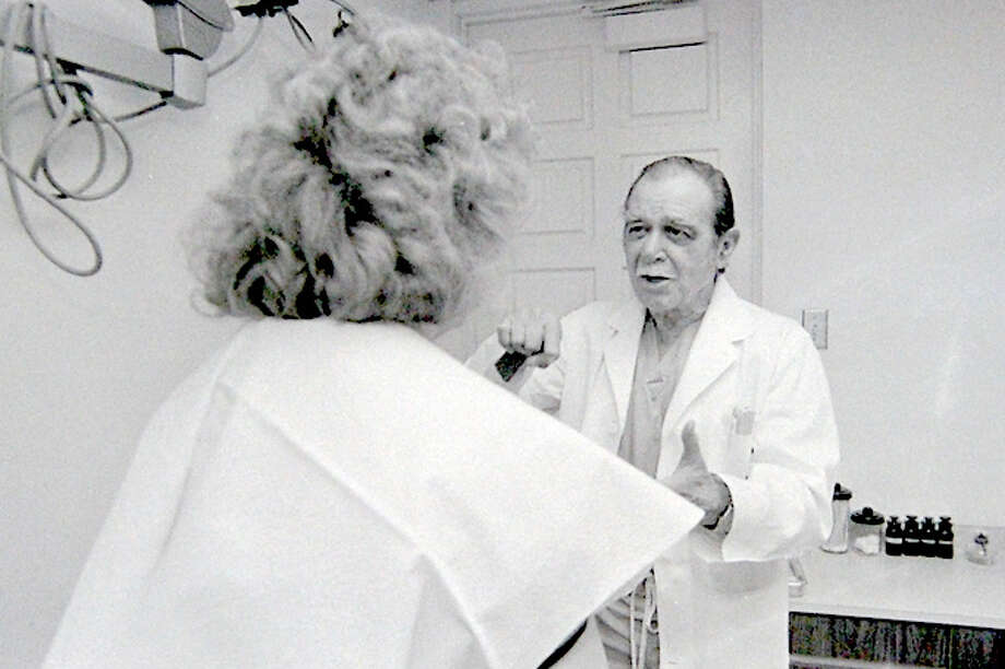 Dr. John Long explains treatment options with a breast cancer victim in this 1987 Herald photograph.