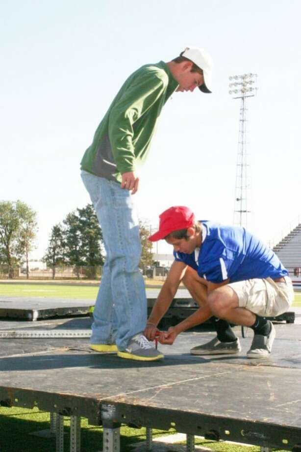 As part of Wayland's Degree of Difference Day on Saturday, WBU students Nick Cormier (right) of Longview and Reid Layton of Seminole serve as part of the work crew assembling the stage for the Plainview Area Go Tell Crusade that begins today and runs through Wednesday at Greg Sherwood Memorial Bulldog Stadium. Photo: Jonathan Petty