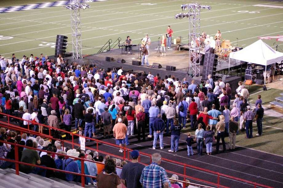 Scores crowd around the stage at Greg Sherwood Memorial Bulldog Stadium in response to the gospel message of Jesus Christ as preached by evanglist Rick Gage at the conclusion of Sunday's Go Tell Crusade. The Billy Graham-style crusade continues nightly through Wednesday, beginning at 7 p.m. More than 2,000 attended the opening night of the crusade on Sunday.