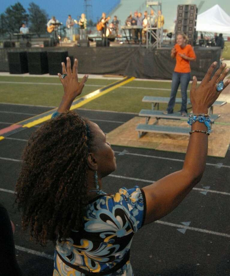 Vivian Finch raises her hands in praise during the worship portion of Tuesday's Go Tell Crusade at Greg Sherwood Memorial Bulldog Stadium. Crowds have averaged around 2,000 people over the first three nights of the crusade and, according to organizers, approximately 200 people had made some sort of public spiritual commitment going into Tuesday's service. Photo: Richard Porter/Plainview Herald