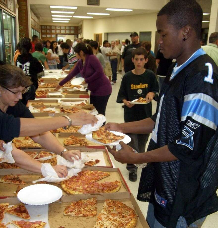 "Kevin Lewis/Plainview HeraldWayland freshman Prince Dawkins of Plainview grabs a slice of the 250 pizzas provided free prior to Wednesday evening's Plainview Area Go Tell Crusade. Originally scheduled to end Wednesday, the crusade has been extended to include services tonight at 7 p.m. at Hutcherson Center, after Friday night's Bulldog football game at the stadium, and 7 p.m. Sunday at ""The Hutch."""