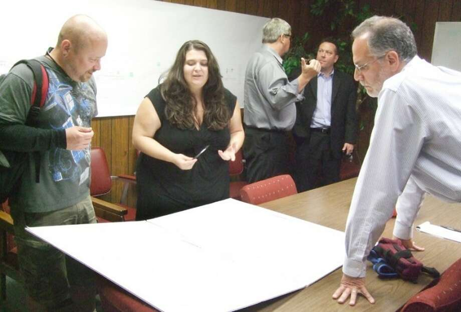 Heather May, new owner of the old Gebo's/Marse & Son building, shows her plans to Plainview Main Street/Tourism Board member Patric Jernigan (left) and Howard Langner, head architect of the Texas Main Street program and state historical commission. In the background are Eric Turner, Plainview Main Street manager, and board member Anthony Brocato, after a meeting on Tuesday. Photo: Shanna Sissom/Plainview Herald