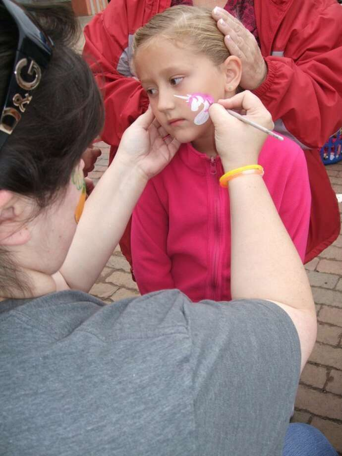 Taylee Watson, 7, of Plainview gets her face painted by Melissa Unfred at Punkin Days on Saturday in Floydada. (See more photos in the Herald and video at www.MyPlainview.com.)