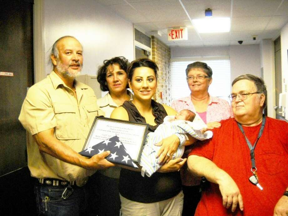 Desiree Law holds her son, Aiden James, as her parents, Robert and Dolores Salinas of Olton (left) and her husband Chase's parents, Jimmy and Glenna Law of Belen, N.M., look on at Covenant Hospital Plainview. Mr. Salinas holds a flag and certificate presented to Aiden by hospital officials in honor of his dad, a U.S. Army soldier in Iraq, being unable to attend his birth. Photo: Courtesy Photo