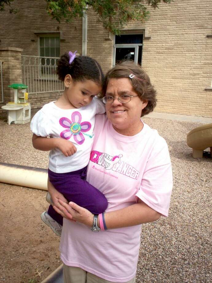 Nicki Bruce Logan/Plainview HeraldTami Vernon, wearing a Susan G. Komen Kick Out Cancer shirt given to her by a nephew, and Janae Douglas share a hug on the playground of the First United Methodist Church Child Development Center where she has worked since 1999. Vernon is a 10-year breast cancer survivor.