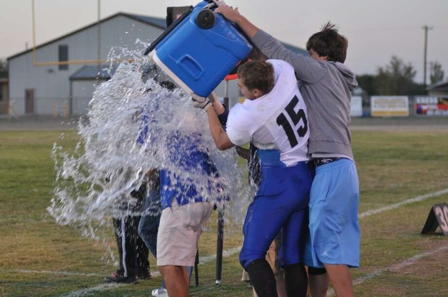 Plainview Christian's Tanner Morton (15) and Drew Johnson (right) dump the water cooler on Plainview Christian coach Humberto Gonzalez after beating the Kress Kangaroo junior varsity 73-32 on Thursday in Kress. Photo: Courtesy Photo By Cathy Landtroop