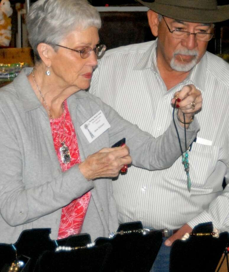 Jane Dickson with My Favorite Things of Plainview shows a necklace to Chuy Dominguez of El Paso during Saturday's Runningwater Draw Arts and Crafts Festival at Plainview's Ollie Liner Center. The festival ends its three-day run today from noon to 5 p.m.