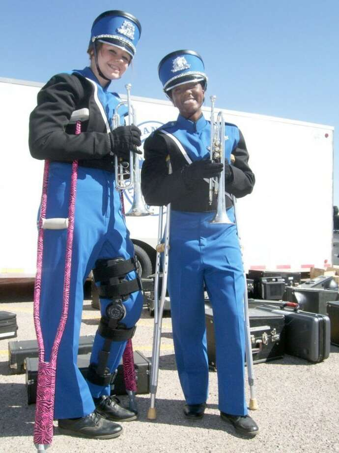 Kaylee Rose (left) and Keyla Rabon can't march but still play with the Olton band despite being on crutches as a result of knee injuries. Both are sophomores, both play the trumpet and they have the same initials (KR).