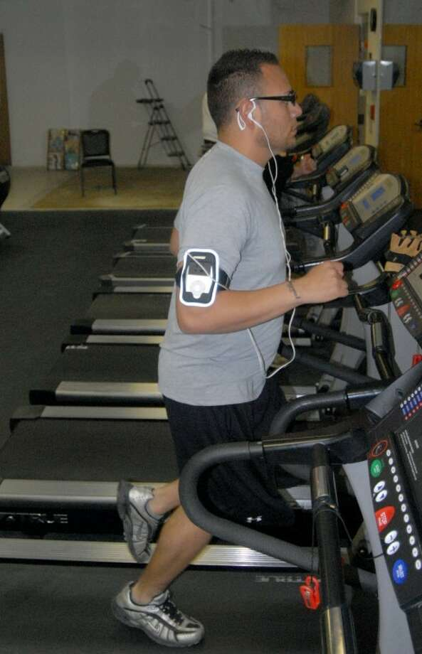 Vincent Gallegos works out in the cardio room at the Plainview YMCA, which shows signs of the expansion work that is being done in the background. Photo: Richard Porter/Plainview Herald