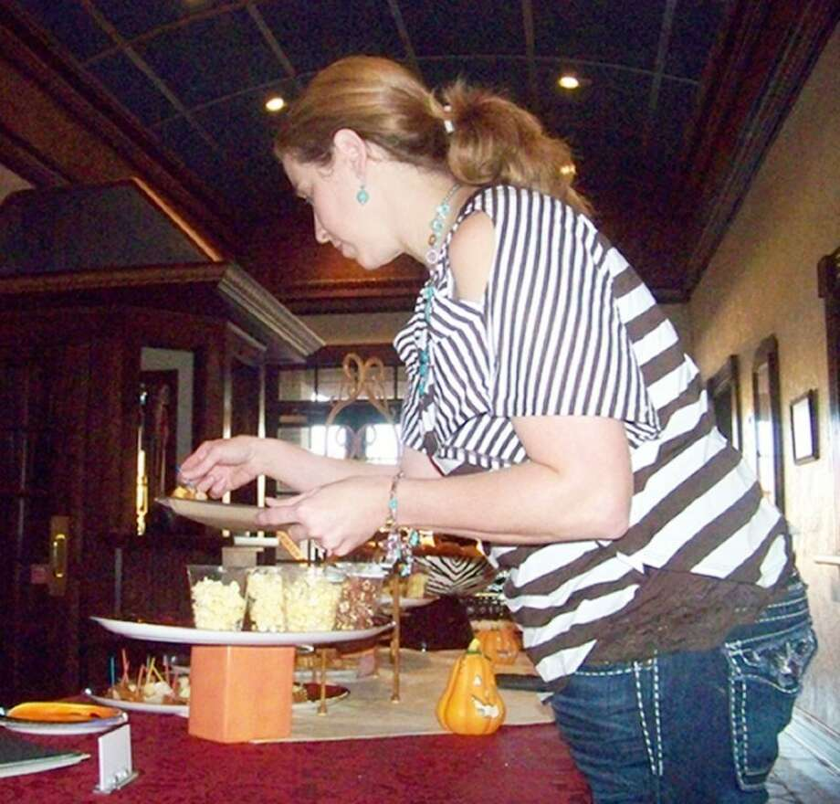 Season's Way owner Heather Hill places caramel apples on dishes for the public during the Chamber of Commerce's Business After Hours mixer at the Fair Theatre Tuesday night. The theatre celebrated its 13th birthday as it was reopened in 1999. Guests were treated to popcorn, caramel apples and pumpkin roll slices courtesy of Season's Way. Southern Elegance catered different types of mini cupcakes.