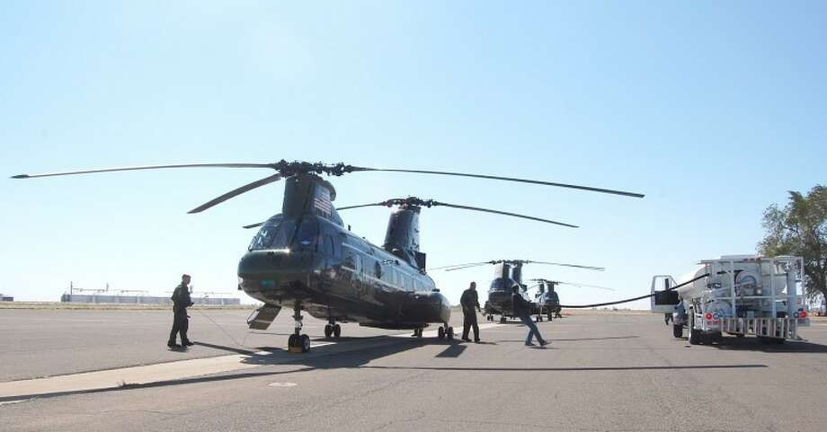 Three Marine helicopters made a refueling stop Tuesday afternoon at Plainview/Hale County Airport while on a flight from Virginia to California. After taking on about 500 gallons of fuel each at Rocket Aviation, the trio departed for Albuquerque, N.M., the next stop on their transcontinental flight. According to Cpt. Brandon Ogden (shown in the interior of the lead helicopter, which was built in 1969), the cross-country flight was expected to take about 20 hours of flying time with an average cruising speeding of 120 knots (138 mph) and above-ground altitude of 1,500 feet. According to Ogden, each helicopter normally has a crew of four - pilot, co-pilot and two crew chiefs. However, 22 Marines, including maintenance and support personnel, are making this journey. The helicopters, which may eventually be replaced by V-22 Osprey tilt-rotor crafts, saw recent military action in Iraq. However, Ogden said, their use in Afghanistan is limited due to higher altitudes. With blades unfolded, Ogden said, the overall length of each craft is 71 1/2 feet. Photo: By DOUG McDONOUGH Plainview Herald