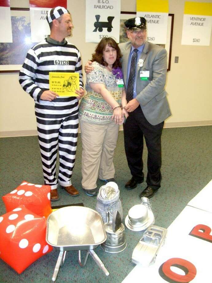 "Renee Branch, lab services manager at Covenant Hospital Plainview, gets taken to jail by Covenant ""cop"" and CEO Alan King (right) while assistant administrator and ""jailbird"" Mike McNutt displays his own booking number. Using an elaborate Monopoly theme, it was all part of the hospital's kickoff to its United Way fundraising campaign as well as its Covenant Cares Campaign. Close to 95 percent of the hospital's 280 employees participate in the fundraising efforts. Last year, employees donated $53,000 - a figure matched by the Hale County Hospital Authority - toward the Covenant Cares Campaign, which goes to pay for hospital equipment and programs. Also, hospital employees last year contributed $43,000 to United Way. Photo: Kevin Lewis Plainview Herald"