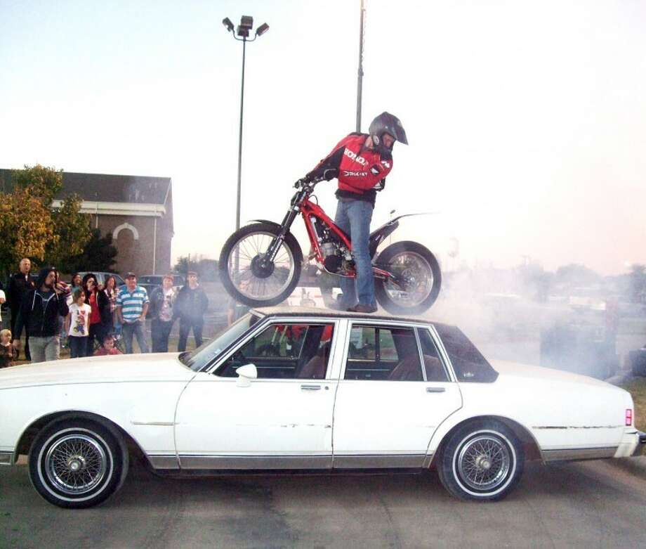 Brad Bennett performs a burnout on top of this old car before he broke out the side windows with the front tire by doing wheelies with his specially-equipped motorcycle during the Real Encounter Outreach performance Wednesday night in front of Harral Auditorium. Photo: Kevin Lewis/Plainview Herald