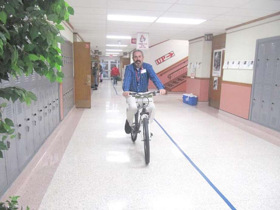 Ash Principal Kelly Priest was caught test-driving a bike later given to a student through the Plainview Rotary Club's perfect attendance program. Counselor Janie Hart reportedly was seen testing out a girl's bike in the school's hallways just prior to Priest going for a spin. Photo: Courtesy Photo By Coralyn Dillard