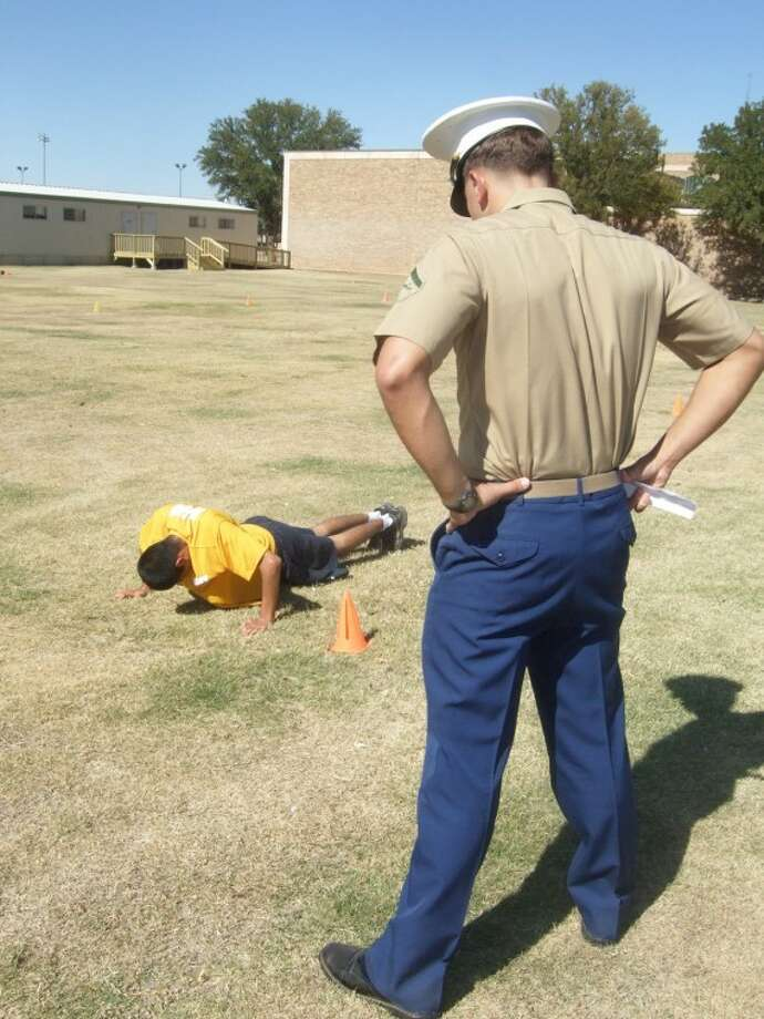 "Plainview High School senior Adrian Flores, a third-year student in the PHS Navy Jr. ROTC program, does push-ups under the watchful eye of Lance Cpl. Anthony Salazar of Amarillo at Saturday's first King Trident Invitational Drill Competition at Wayland Baptist University. Six area JROTC units participated in the competition, which featured an obstacle course that included 60 push-ups, 60 sit-ups, 40 jumping Jacks and a series of sprints. ""It killed me,"" said Flores, who finished the course in just more than six minutes. (See related video.)"