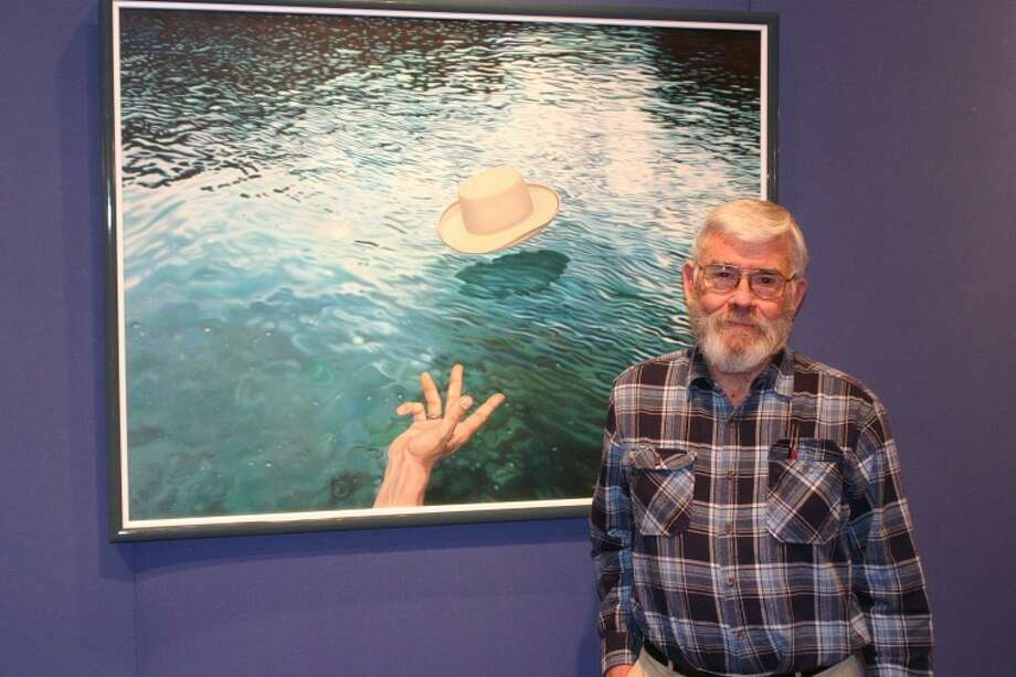 "Jonathan Petty/Wayland Baptist UniversityJoe Garnett of Lockney stands by his painting ""Hat in Water,"" which is hanging in Wayland's Abraham Art Gallery. Garnett will display his work in ""Then and Now: The Works of Joe Garnett, a Retrospective"" until Dec. 3."