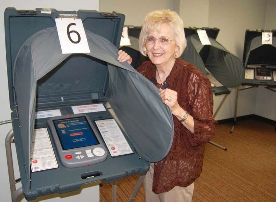 Mary Helen Cross, a local election judge, displays one of the voting machines available for early voters in the Texas Constitutional Amendments Election. Early voting began Monday and continues from 8 a.m.-5 p.m. weekdays through Nov. 4 in the Hale County Courthouse basement. Early ballots also can be cast at the Abernathy, Hale Center and Petersburg city halls. Election Day is Nov. 8. Turnout for early voting has been very light, according to election workers, with 18 ballots cast at the courthouse on Monday and another 13 on Tuesday. Voting totals from other county locations were not available this morning. Photo: By DOUG McDONOUGH Herald Managing Editor
