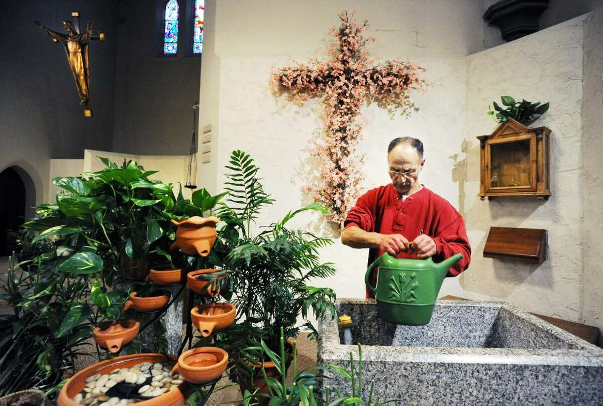 Jim Sarantos, with facilities maintenance, waters the plants at St. Maurice Catholic Church in Stamford, Conn. on Tuesday April 27, 2010.