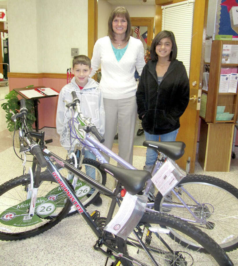 Sandra Aven of the Plainview Rotary Club presents bikes to Braydon Bradford and Leslie Montes of Ash Sixth Grade Learning Center as part of the club's perfect attendance program for the first six weeks of school. Other winners of bikes or iPods were: Coronado, Pedro Fabian-Bautista and Alma Avalos; Lakeside, Arika Raybal and Eddy Ramirez; Estacado, Khyra Riddley and Oliver Gutierrez Molina; Houston School, Annaliza Molinar; PHS, Ethan Anderson, Brigette Longoria and Kristyn Robinson.