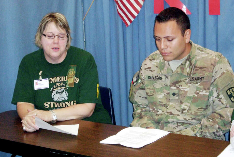 Spc. Vincent Gallegos spoke with Thunderbird Elementary School counselor Dana Marchman during morning announcements Thursday. Gallegos was chosen as Thunderbird's adopted soldier for the school year and will receive letters and care packages from the students while serving overseas. Gallegos' daughter, Sarayah, is a kindergartner at Thunderbird. He returns to Afghanistan on Sunday. Photo: Jessica Thornton/Plainview Herald