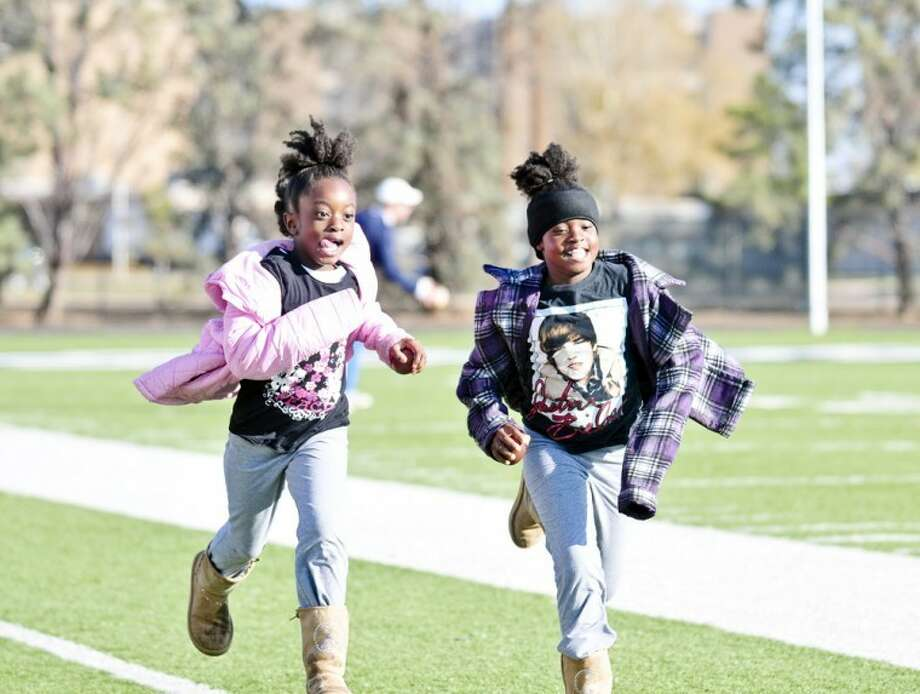 Ashton (left) and Autumn Paige, daughters of Wayland football assistant coach Anton Paige, race on the sidelines at Greg Sherwood Memorial Bulldog Stadium on a chilly Saturday morning before the Pioneers held an intrasquad scrimmage to mark the end of their football season.