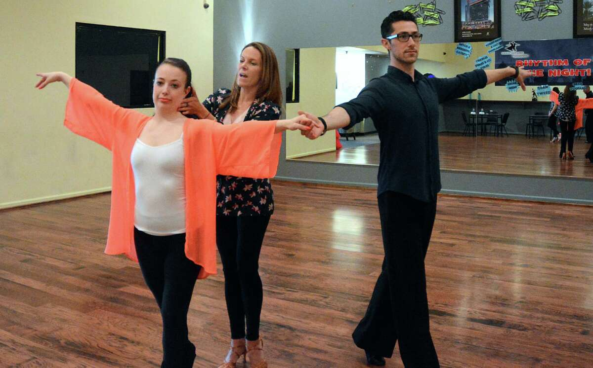 Stephanie Schlueter, owner of the Fred Astaire Dance Studio corrects the head position of instructor Amber Osborn as she dances with Jhondarr Lopez, both of The Woodlands, during a training session at the dance studio.