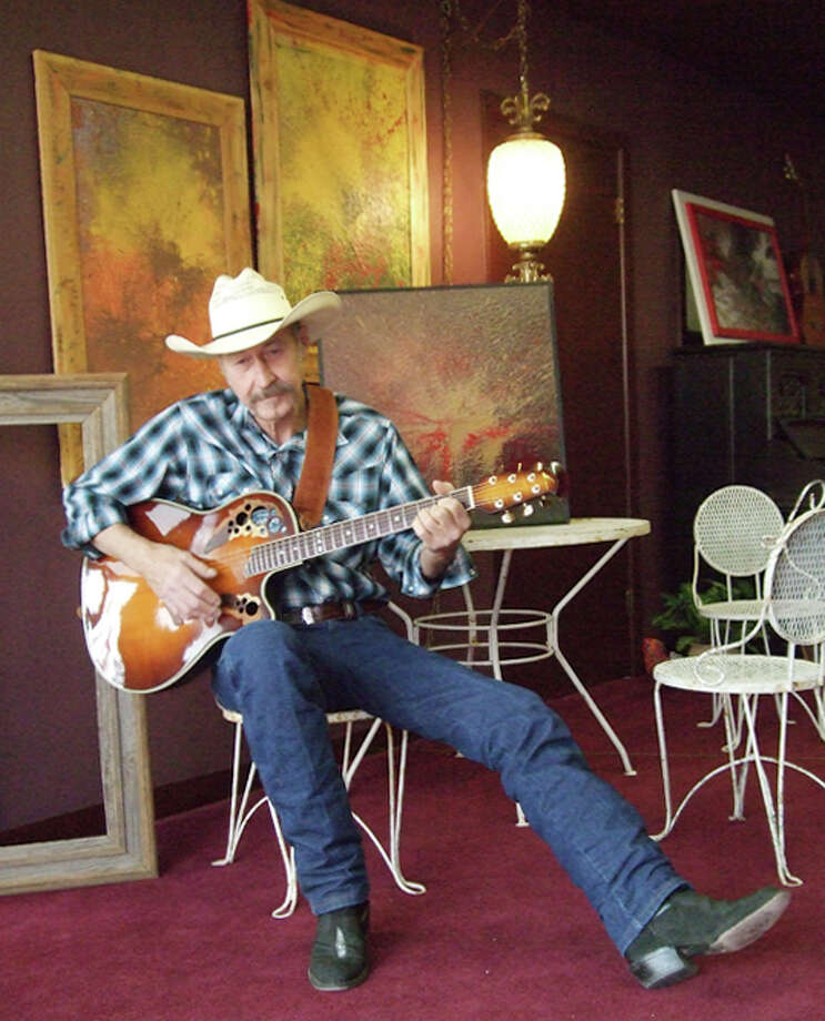 Ronny D. Green strums his guitar in front of a display of his paintings now being shown at The Wall Gallery, 803 Broadway. Photo: Gail M. Williams | Plainview Herald