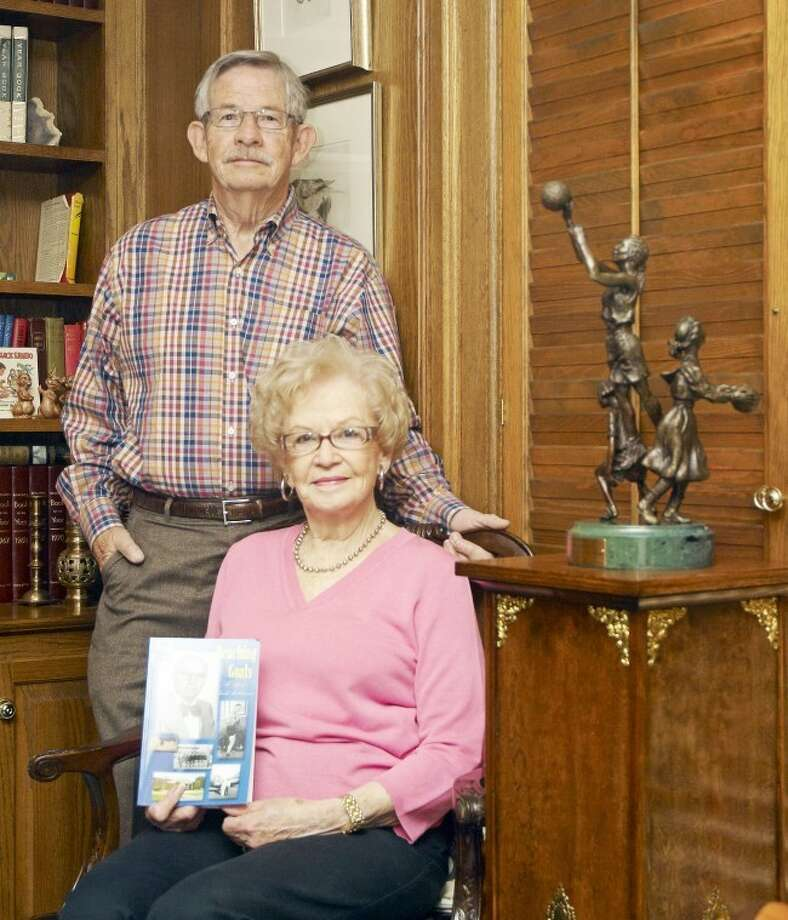"Jason Johnson/Plainview HeraldMike Hutcherson stands behind his mother Wilda Hutcherson Redin, who is holding a copy of her book, ""Reaching Goals, The Life of Claude Hutcherson,"" written about her late husband and Mike's father. On the pedestal next to them is a bronze statue presented to Wilda at Claude's induction into the Women's Basketball Hall of Fame in 2003."