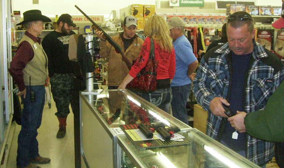 Gebo's sales associate Ted Porter (left) is busy helping customers buying guns and ammo during Black Friday's sales event. Photo: Shanna Sissom/Plainview Herald