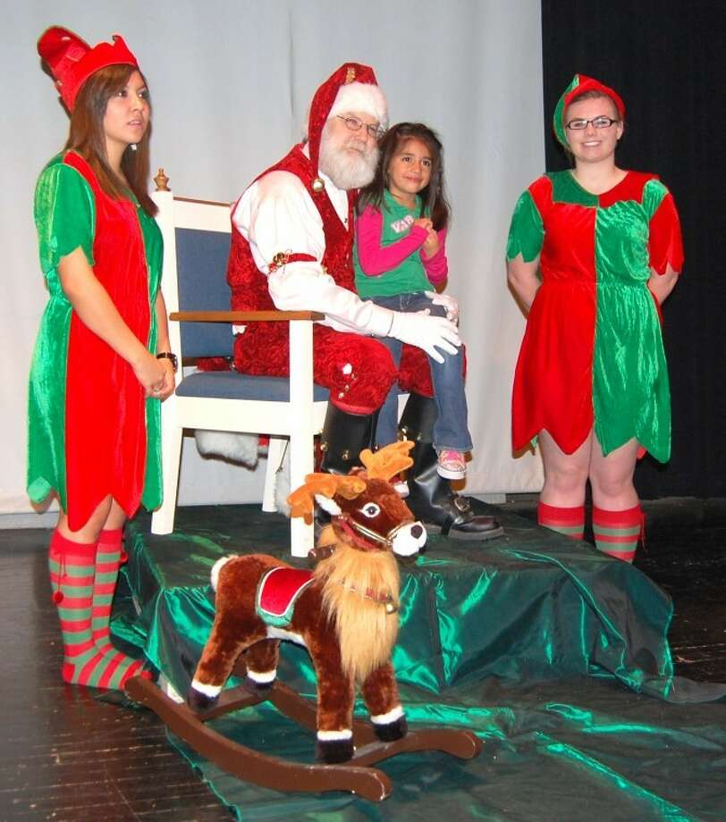 In this Dec. 2011 file photo, Genesis Rogers,  daughter of Jaime Rogers of Plain view, reviews her Christmas wish list with Santa (aka Rodney Watson) at the pre-parade party at the Fair Theatre. Santa's helpers are Sofia Zuniga (left) and Kelsey Mires.