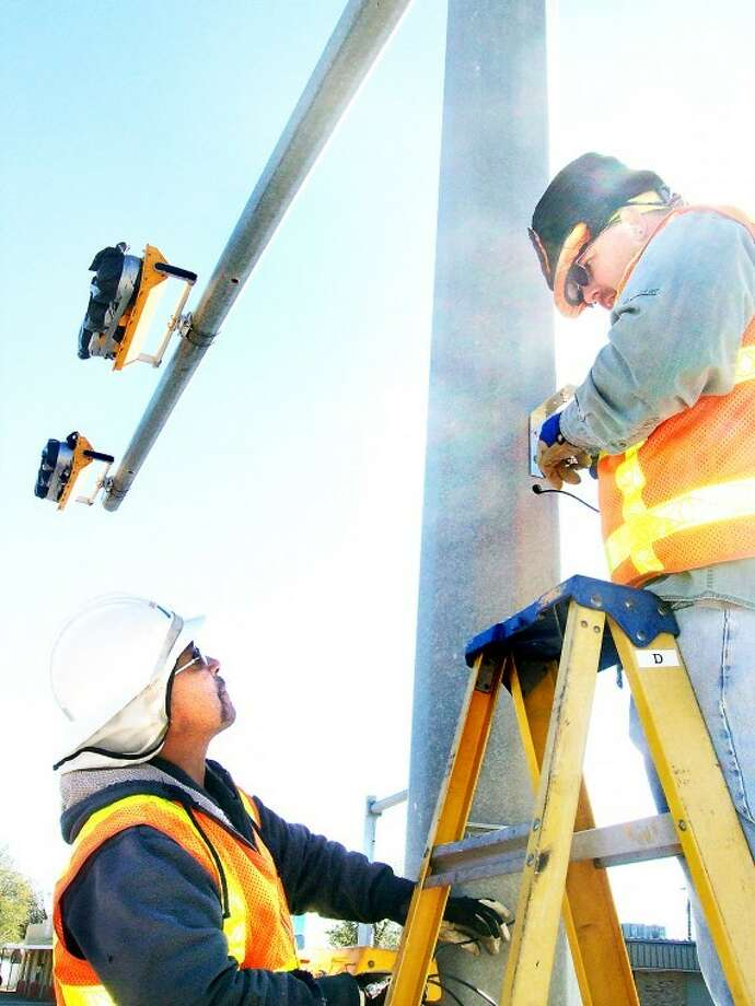 Gary Moore (right) and Ernie Garcia, both with the Texas Department of Transportation in Lubbock, work to install equipment response traffic signals outside Fire Station 2 on Quincy Street. A project of TxDOT and the City of Plainview, signals will alert motorists when emergency vehicles are leaving and returning to the station. Lights, expected to become active this week, will remain green until red lights are activated for an emergency.