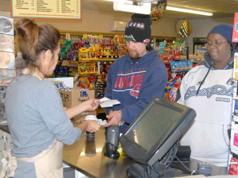 Allsup's clerk Susan Valenzuela sells Juan Espinso and Tammy Collins Powerball tickets Tuesday. The Powerball has rolled over 16 times since Oct. 6, propelling tonight's jackpot to a prize expected to exceed $500 million. Both Espinso, a meat-cutter at Cargill, and Collins, who cares for rehab patients, said they would keep their jobs if they hit the half-billion-dollar jackpot. Photo: Shanna Sissom/Plainview Herald