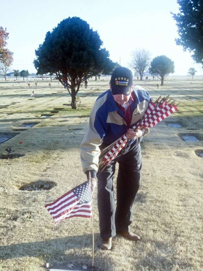 Korean War veteran Gerald Chambers places a U.S. flag in a holder at a veteran's grave at Plainview Cemetery in honor of Veterans Day. Chambers volunteers every year on Memorial Day and Veterans Day to place flags on graves. Photo: Jessica Thornton/Plainview Herald