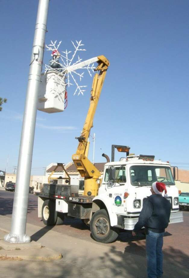 City of Plainview employees Felix Ruiz (on cherry picker) and Richard Alvis work Monday putting up new Christmas lights. About 40 6-foot-tall snowflake lights are going up on Broadway, Ash and Sixth streets. The lights — valued at more than $10,000 — were purchased at a discounted price during the off-season early this year. Photo: Shanna Sissom/Plainview Herald