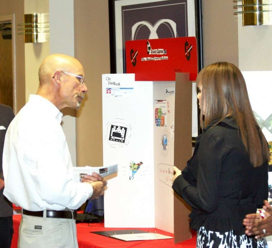 Plainview Chamber of Commerce President Kenneth Hooper talks with Plainview High School student Kristen True about her project at Tuesday's fifth annual Ogallala Commons Regional Youth Entrepreneur Fair. Plainview students took home more than $3,000 in cash prizes. Photo: Courtesy Photo By Eric Turner