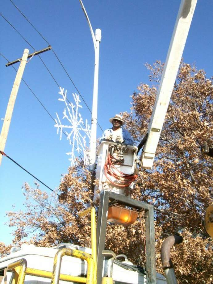 City of Plainview employee Felix Ruiz checks bulbs on a new downtown street Christmas decoration. Xcel Energy and S&S Electric also have been troubleshooting the new decorations this week to make sure all lights are functioning for tonight's Christmas parade, which begins at 6:30 p.m. It will travel from Broadway Park to the Santa Fe depot. Photo: Shanna Sissom/Plainview Herald