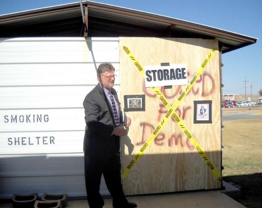 Covenant Hospital CEO Alan King designates the employees' smoking shelter as being out of business. It will be used for storage after the hospital became a tobacco-free campus last week.