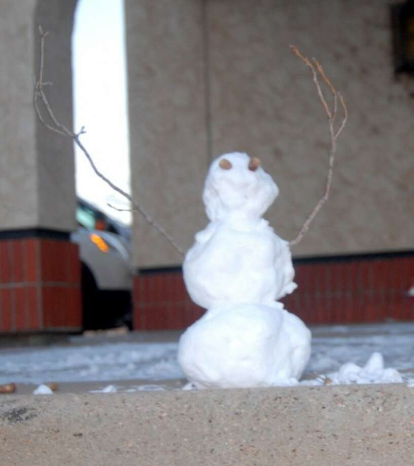 A diminutive snowman, built from the season's first snowfall, could be seen on the curb in front of the Herald early Monday. No one came forward Monday claiming credit for the snowman, which was less than a foot tall. Photo: DOUG McDONOUGH