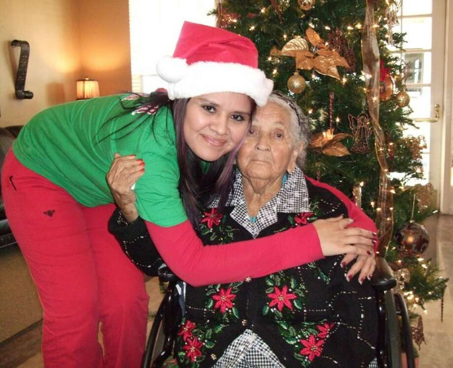 Licensed vocational nurse Maria Mendoza (left) hugs Alfonza Hernandez by the Christmas tree in Prairie House Living Center. Hernandez decided to wear a Christmas sweater Thursday, and was seen rolling down the halls in her wheelchair as residents at the center prepare to celebrate Christmas together. Photo: Shanna Sissom/Plainview Herald
