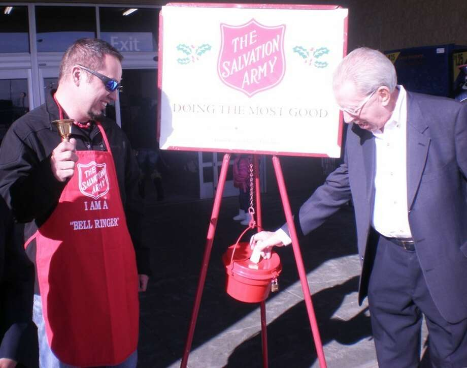 Mayor John C. Anderson (right) offers the first donation as Troy Valdivia rings the bell to kick off The Salvation Army's annual red kettle campaign on Friday outside Walmart Supercenter. The Salvation Army has been ringing the bell here since 1929.