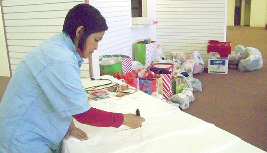 "Salvation Army Capt. Adriana Martinez numbers bags, into which gifts will go in once they are ready. The gifts in the corner is what Martinez has received from the community. The deadline to adopt an ""angel"" is Dec. 21. Photo: Jessica Thornton/Plainview Herald"