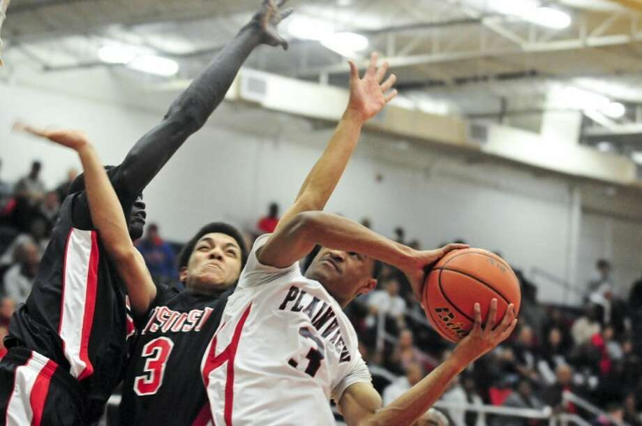 Plainview's Jaylon Jackson (right) is double-teamed by Tascosa's Jaeem Toombas (3) and Francis Aguir as Jackson drives for a layup in Monday's game at the DogHouse. Photo: Ryan Thurman/Plainview Herald