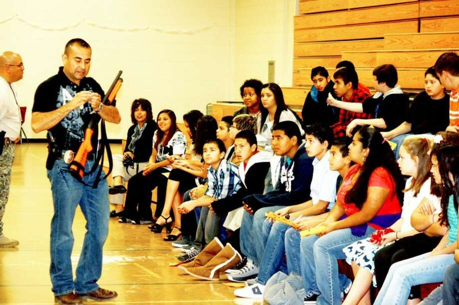 Coronado Junior High students watch Plainview Police Department SWAT team member Lt. Jamie Salinas demonstrate weapons and gear police use when responding to emergencies. Photo: Jan Seago/Plainview ISD