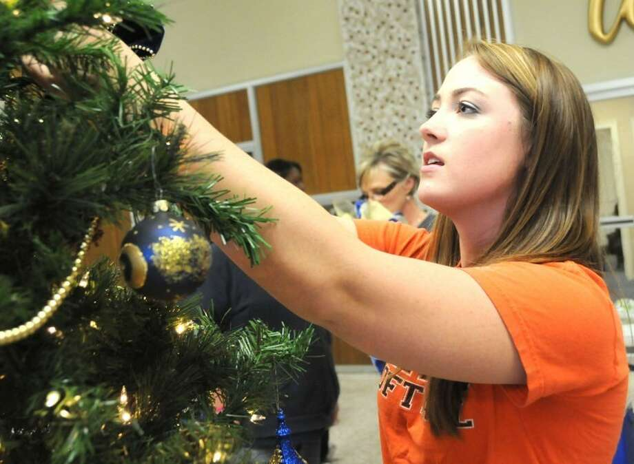 Jenna Swift, a member of Wayland's Alpha Delta Kappa sorority, helps decorate the Christmas tree inside Gates Hall. Members of Alpha Delta Kappa, Sigma Phi Lambda sorority and Kappa Upsilon Chi fraternity decorated the tree Friday evening.