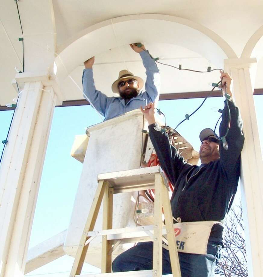 "Felix Ruiz (left) and Ricky Garcia with the City of Plainview string lights around City Hall on Tuesday in preparation for the Festival of Lights Parade set for 6:30 p.m. Dec. 1. Entry forms for the downtown parade are available at the Plainview Chamber of Commerce, 1906 W. Fifth. Prizes will be awarded for best small float, best large float, best decorated entry, judges' choice and best representation of theme, ""A West Texas Christmas."" Entries must have a registration form and a contest flag from the Chamber. Entry is free. Photo: By SHANE HARRELL City Of Plainview"