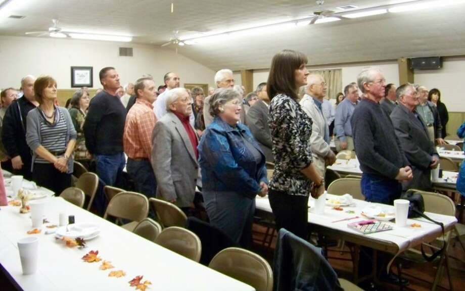 "Audience members stand to show honor and thankfulness to our country as Travis Thornton closed out the Edmonson Farm Dinner by singing ""Proud To Be an American."" Photo: By JESSICA THORNTON Plainview Herald"