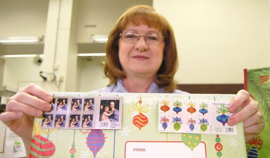 Postal Clerk Vicki Hayes displays two of the more popular holiday stamp designs this Christmas season at the Plainview Post Office. Postal holiday deadlines for sending packages through the U.S. mail for pre-Christmas delivery include: Parcel Post, Dec. 5; First Class, Dec. 20; Priority, Dec. 21; and Express, Dec. 22. For military addresses the deadlines are: Parcel Airlift Mail, Dec. 3 (Dec. 1 for zip code 093); Priority, Dec. 10 (Dec. 4 for zip 093); First Class, Dec. 10 (Dec. 4 for zip 093); and Express, Dec. 18 (zip 093 not available).