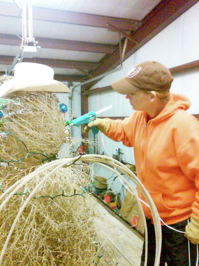 Lisa Wright uses a glue gun to put the finishing touches on a tumbleweed snowman that will adorn the Plainview 4-H Club float in tonight's Christmas parade. Judging starts at 5:30 p.m. with the parade, sponsored by the Plainview Chamber of Commerce, stepping off at 6:30 p.m. from Broadway Park. More than 40 entries will travel north on Broadway to the train depot. Santa will make an appearance at a free pre-parade party from 4:30-6:15 p.m. at the Fair Theatre. That event is hosted by the Hale County Literacy Council.  Photo: Priscilla Hooper/Hale County 4-H