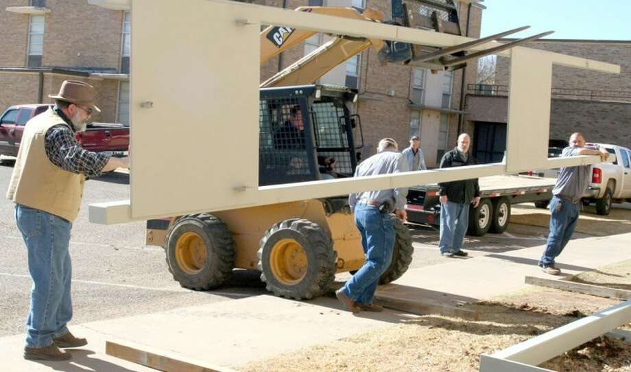 Wayland Director of Maintenance David Murphree uses a forklift Monday to unload part of the tower that will support a wind turbine on the roof of the Moody Science Building while Danny Murphree scrambles to move a beam in place on which the tower will rest. The two are joined by WBU Dean of Mathematics and Science Dr. Herbert Grover (left), biology professor Dr. Randy Craig (back), Associate Dean of Mathematics and Science Dr. Bill Hahn, and maintenance supervisor Robert Lucero. The turbine will be used for research and student training, and Grover and Craig will teach a Renewable Energy Technologies class on Tuesday evenings in the spring. According to Grover, while Wayland students will be given first priority on filling the class, it will be open to the public. Grants for the project include $20,000 from the Formby Foundation and $1,500 from H&H Farms.   Photo: Richard Porter/Wayland Baptist University