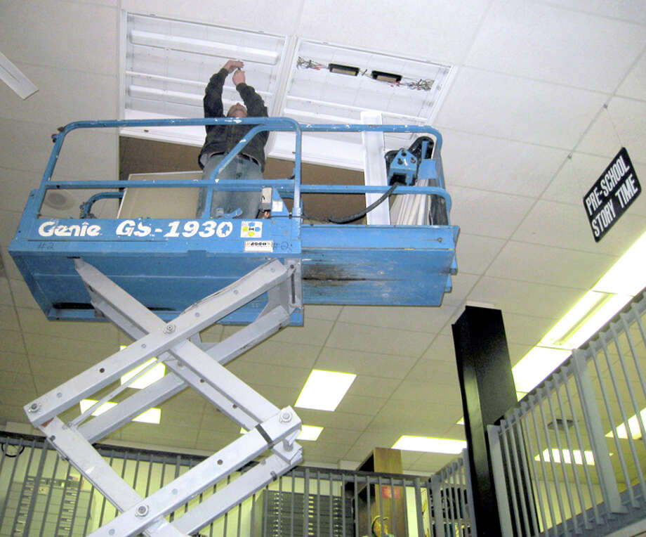 Blake Haney, an electrician with City Electric, installs fluorescent lights at Unger Library. The City of Plainview received an $86,000 federal grant as part of the American Recovery and Reinvestment Act. The Energy Efficiency and Conservation Block Grant will fund new lighting throughout the building as well as double-pane windows for the east part of the library.